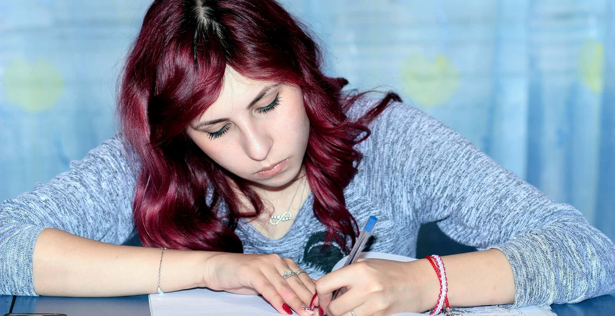 [Image description: A woman with pale skin and red hair taking an exam] via Pexels