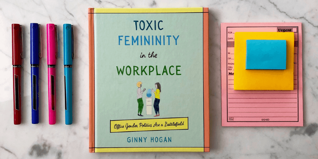 "On a marble top lies the book ""Toxic Femininity in the Workplace"" by Ginny Hogan. On its right is a pile of sticky notes and, on its left, four colored pens."