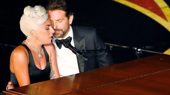 Lady Gaga and Bradley Cooper at the 2019 Oscars performing their song 'Shallow' at a piano with their eyes closed and leaning into each other.