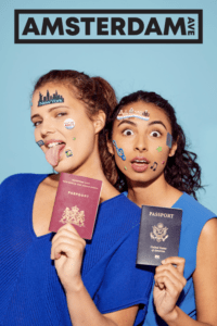 Two young brown women face the camera with passports in hand. On the right, dark-haired Kyran looks suprised. On the left, brown/blonde Maya sticks her tongue out at the camera. Both women are covered in travel stickers.
