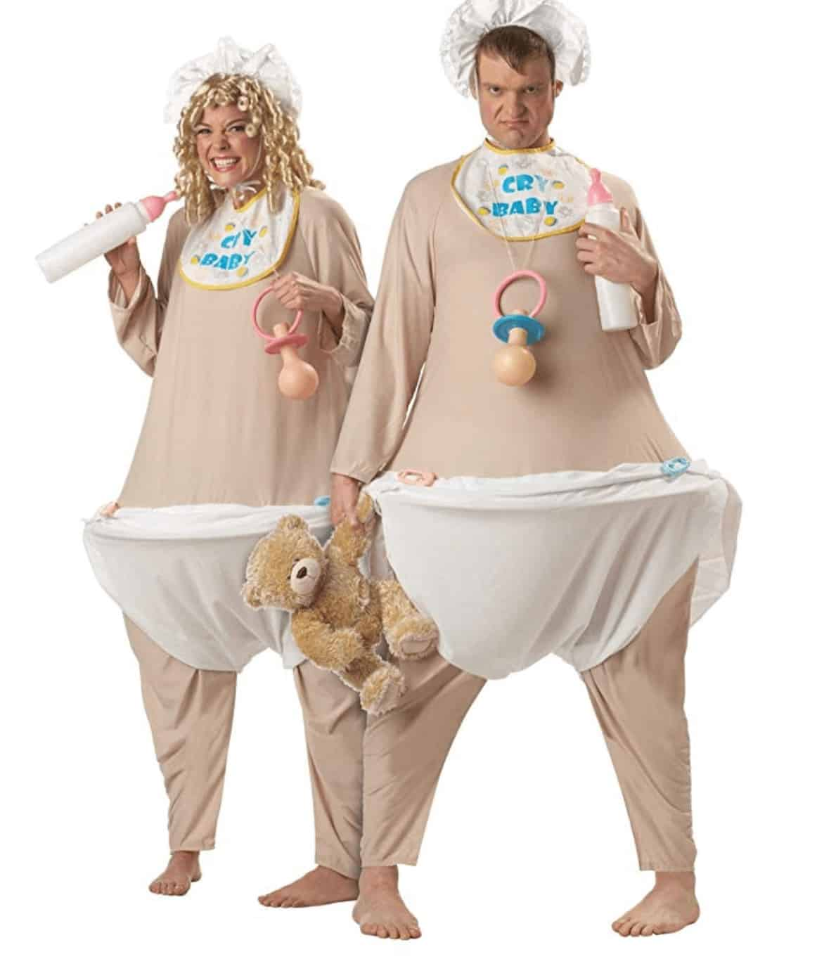 A man and a woman wearing beige baby costumes with wigs and baby accessories. They're holding a milk bottle, a pacifier, and a teddy bear.