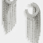 A pair of large silver rhinestone-studded statement earrings.