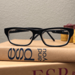 A pair of clear rectangular glasses with black frames atop a pile of books.