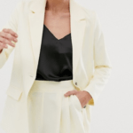 A model wears a pale yellow blazer over a satin black top with matching tailored shorts.