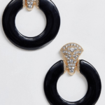 A pair of earrings with a gold and rhinestone fastening and front-facing black hoop.