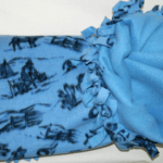 A blue fleece blanket with black patterns drawn-on.