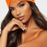 A model with straight brown hair wears an orange turban.