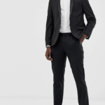A model wears a black tuxedo with a white shirt and black bow tie.