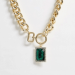 A thick gold chain-link necklace with a large rectangular green stone.