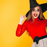 [Image description: A woman is dressed in a halloween costume consisting of a red top, black witch's hat, and a pale gray skirt.] Via senivpetro on freepik