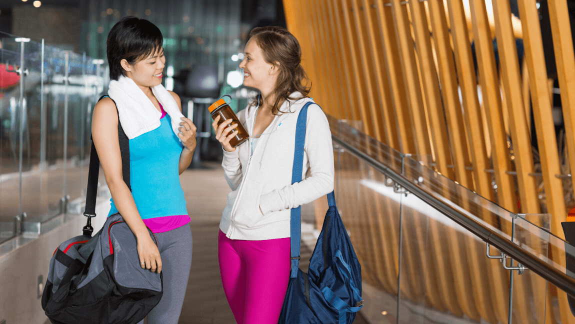 Two women dressed in workout gear are standing, chatting. They each have a gym bag on their shoulder.