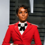Musician and actor Janelle Monae stands before a black and white background, with her hands clasped in front of her. She is wearing a long red suit-jacket with a white shirt and black statement collar, and is gazing to her left.