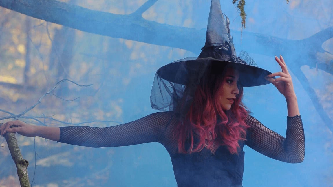 A pink-haired woman is standing amidst fog, out in the woods. She's dressed in black with a pointy hat on top her head.
