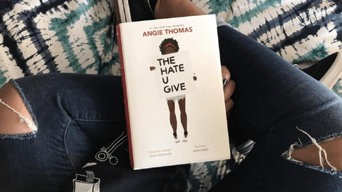[Image description: On a set of jean-clad folded legs rests a copy of The Hate U Give. The cover is white with an illustration of a black teen holding a sign with the book's title on it.] Via fearlessly-fictional on Tumblr