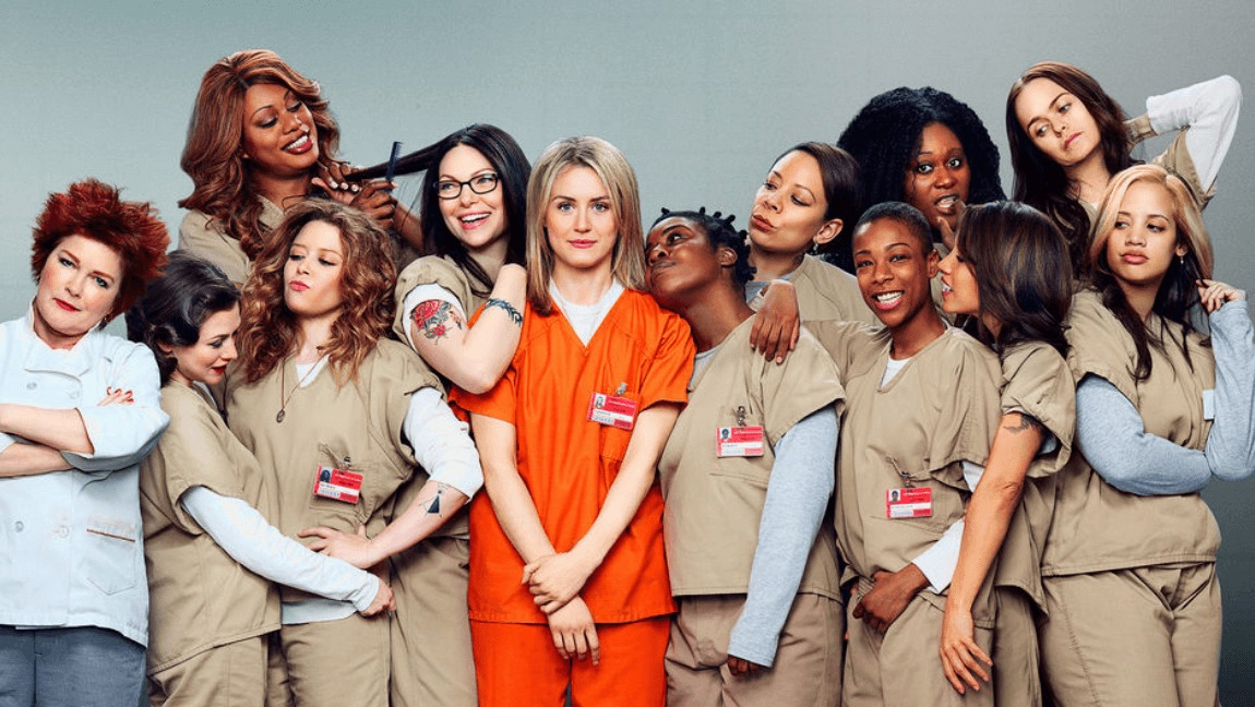 A group of women in prison jumpsuits stand smiling and laughing. In the middle in orange is a blonde, white woman - Piper Chapman.