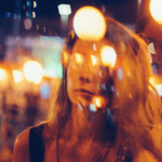 [Image description: Woman looks through the splattering of lights, her reflection shining back to her.] Via Unsplash