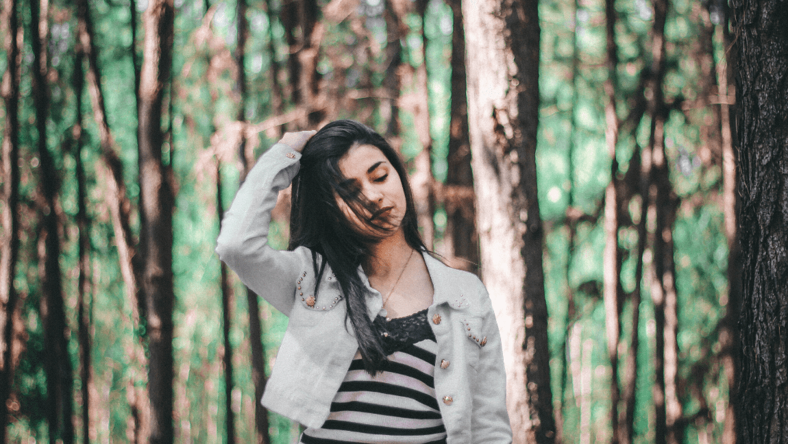 [Image description: Brunette woman in a forest] via Unsplash