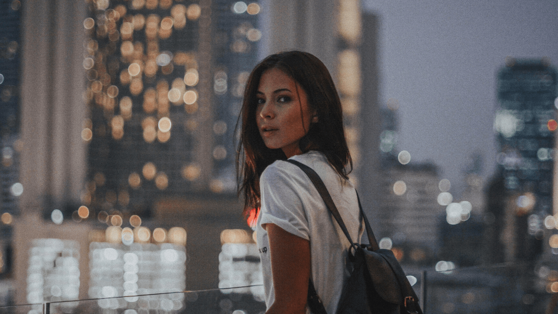[Image description: Woman looks back in a dark city landscape.] via Unsplash