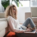 [Image description: Woman with curly hair sits on the floor with a laptop.] via Unsplash
