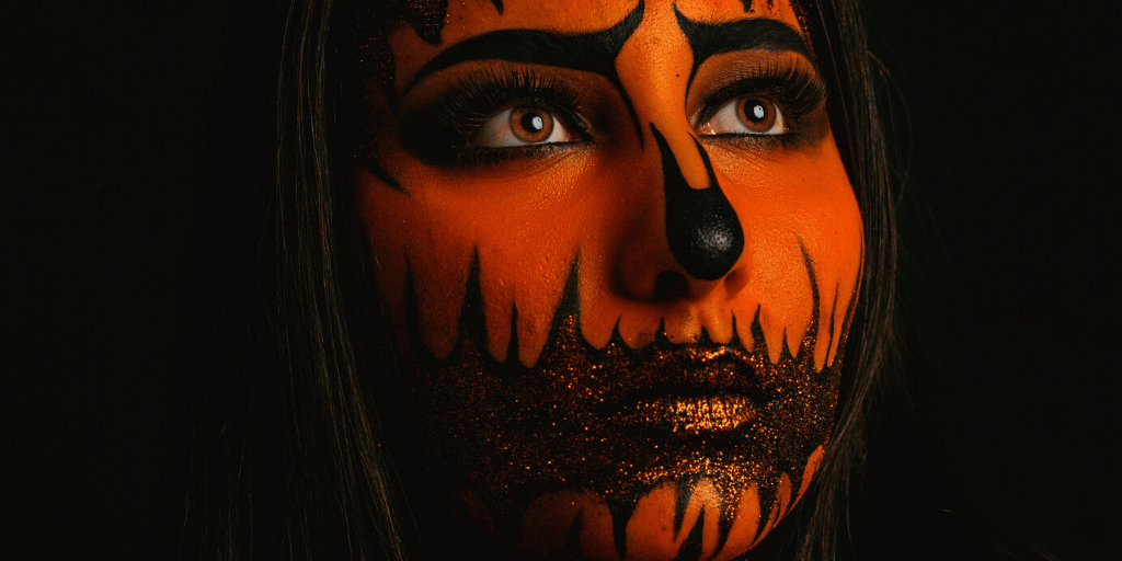 A girl wearing black-and-orange Halloween makeup looks away from the camera.