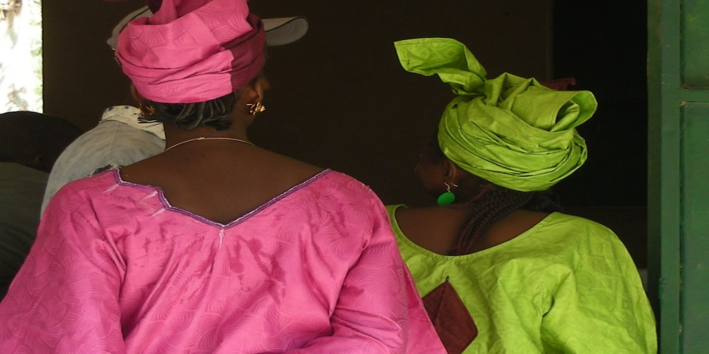 Two women side-by-side with their backs to the camera, one in a bright pink dress and the other in lime green.