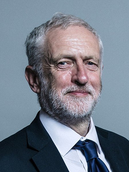 Jeremy Corbyn, a white man with grey hair and a short beard, is smiling at the camera