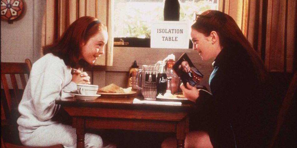 "Two red-headed girls sit at a table labeled ""Isolation Table,"" leaning toward each other and smiling. One is holding a photo of an older man."