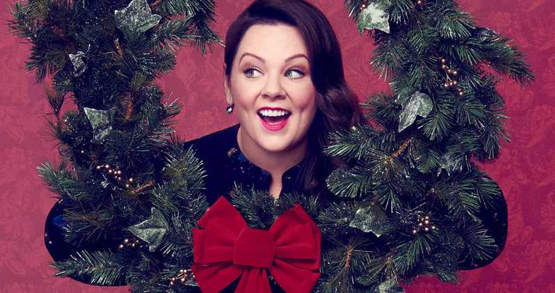 A brunette woman smiles joyously as she pokes her head between a wreath.