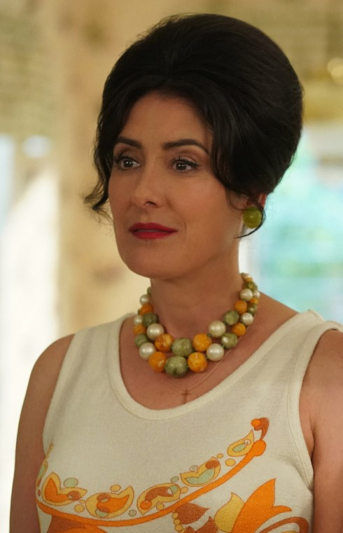 A dark-haired woman - Sheila Mosconi - in a sleeveless top and a large, beaded necklace stares ahead.