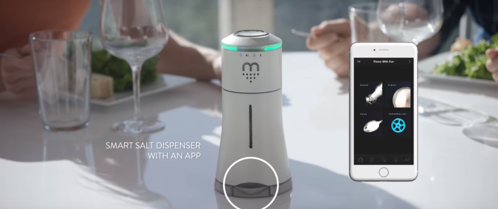 "A screenshot from a promotional video, showing a cylindrical device on a table, floating text that says ""Smart salt dispenser with an app"", and a floating phone on the right."