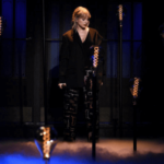 "A still of Taylor Swift performing ""False God"" on SNL in October 2019 against a dark background."