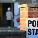 A white 'Polling Station' sign is on a brick pillar as someone in a white hat and grey jacket is entering a building in the background