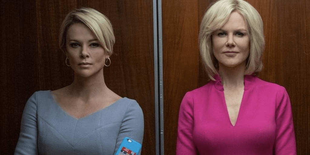 [Image description: Two blond, white female employees, one dressed in light blue, one in pink, standing in an elevator.] Via Bombshell