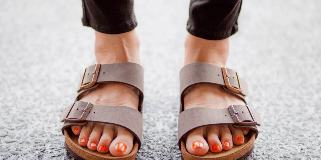 A woman wearing black jeans and tan Birkenstock sandals with orange nail polish on her toes.
