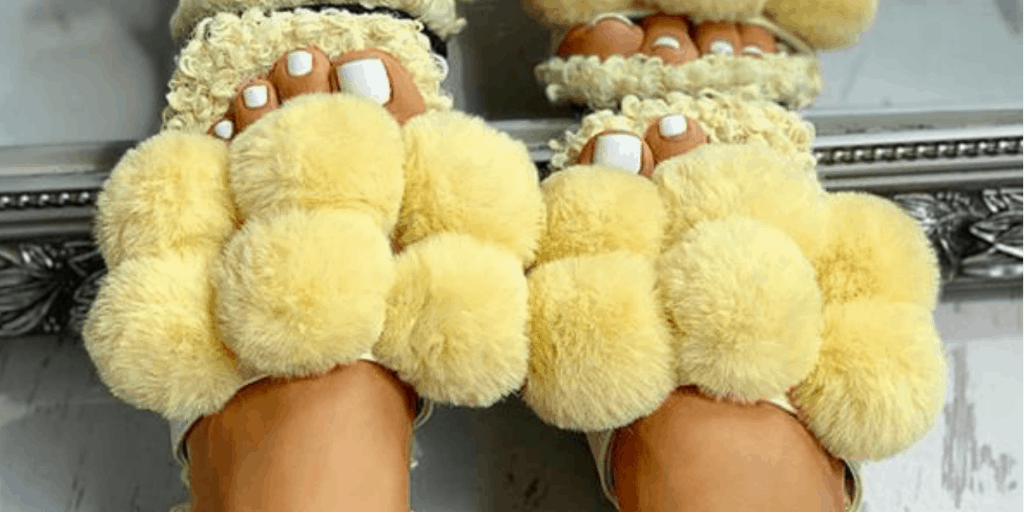 A woman with toenails painted bright white is wearing sandals covered in fluffy yellow pom-poms.