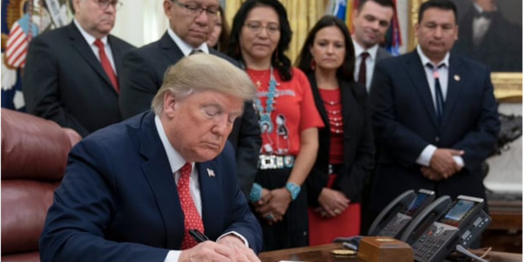 [Image description - Image of President Donald Trump signing a bill into action.] via The Guardian.