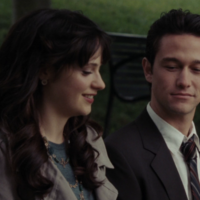 Actress Zooey Deschanel and Actor Joseph Gordon sitting on a park bench, talking and smiling at each other.