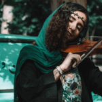 A girl dressed in green, plays the violin.