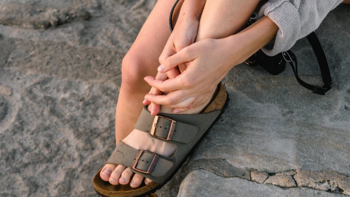 A foot wearing Birkenstock sandals is perched on a rock.