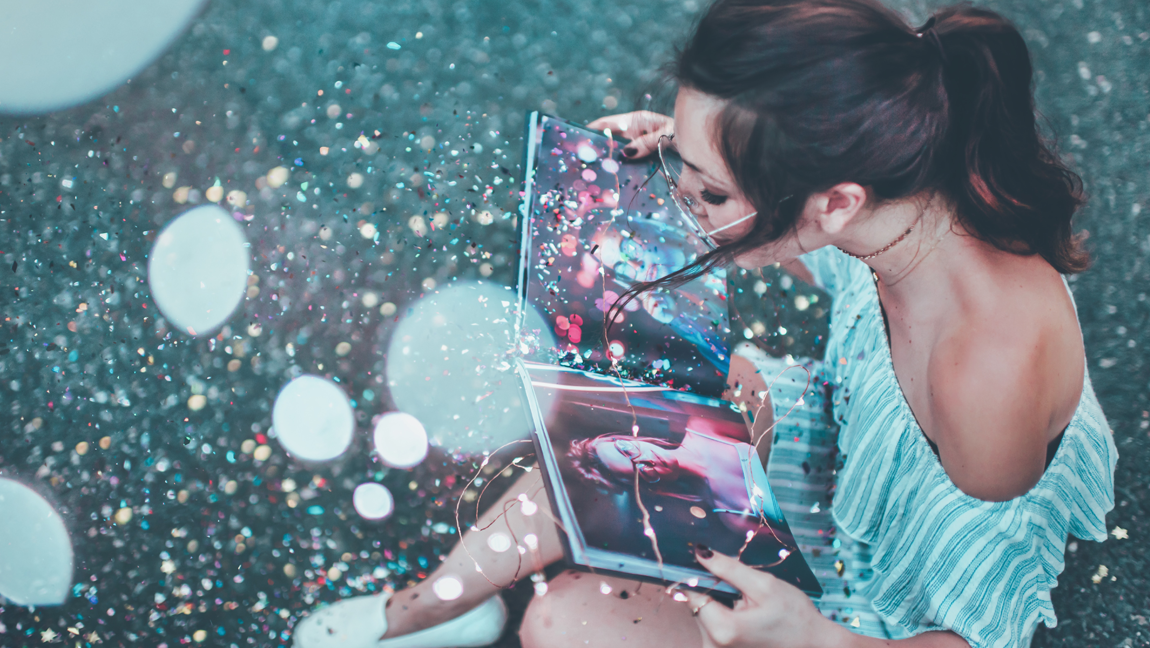 An image of a girl sitting on grass with a photo book in her lap, surrounded by glitter in the air.