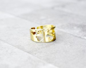 Golden ring with a cut-out of the world map