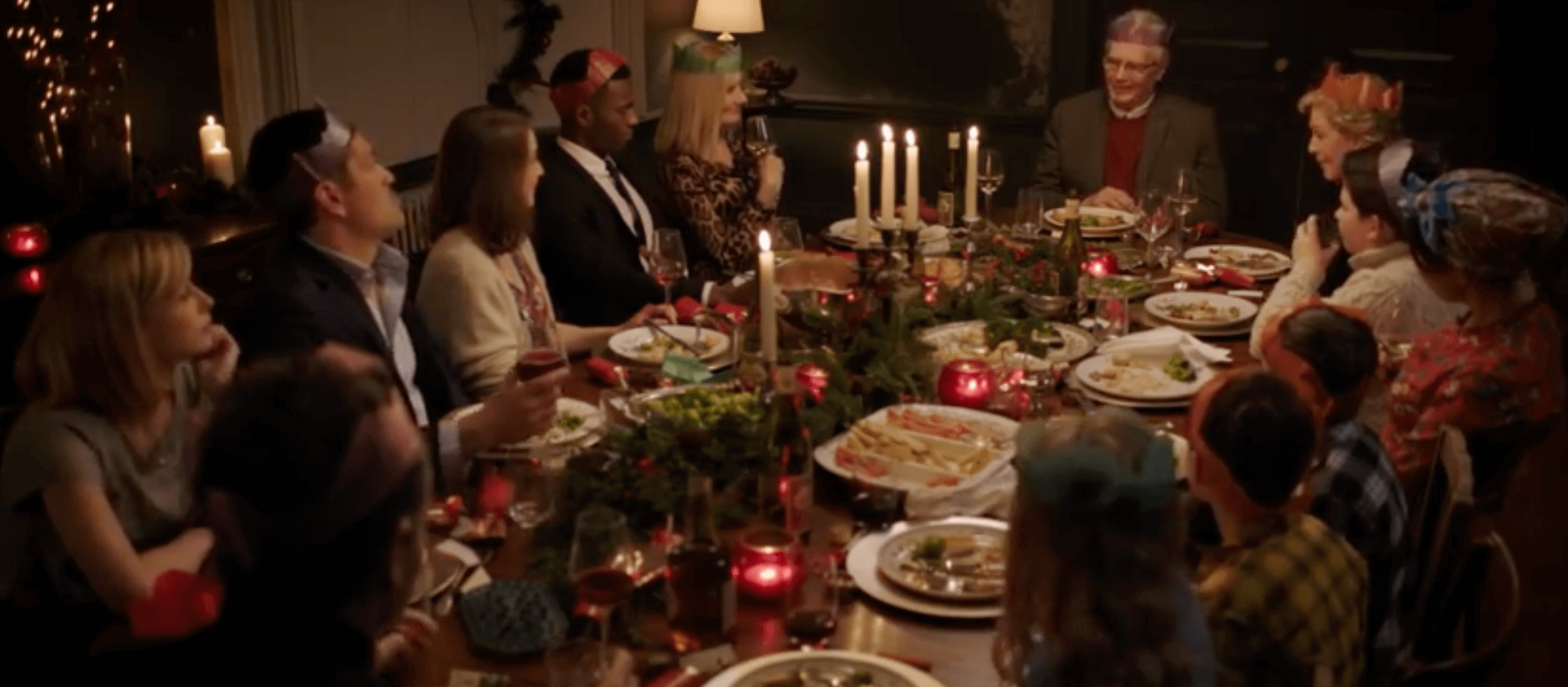 A large family is seated around a Christmas dinner.