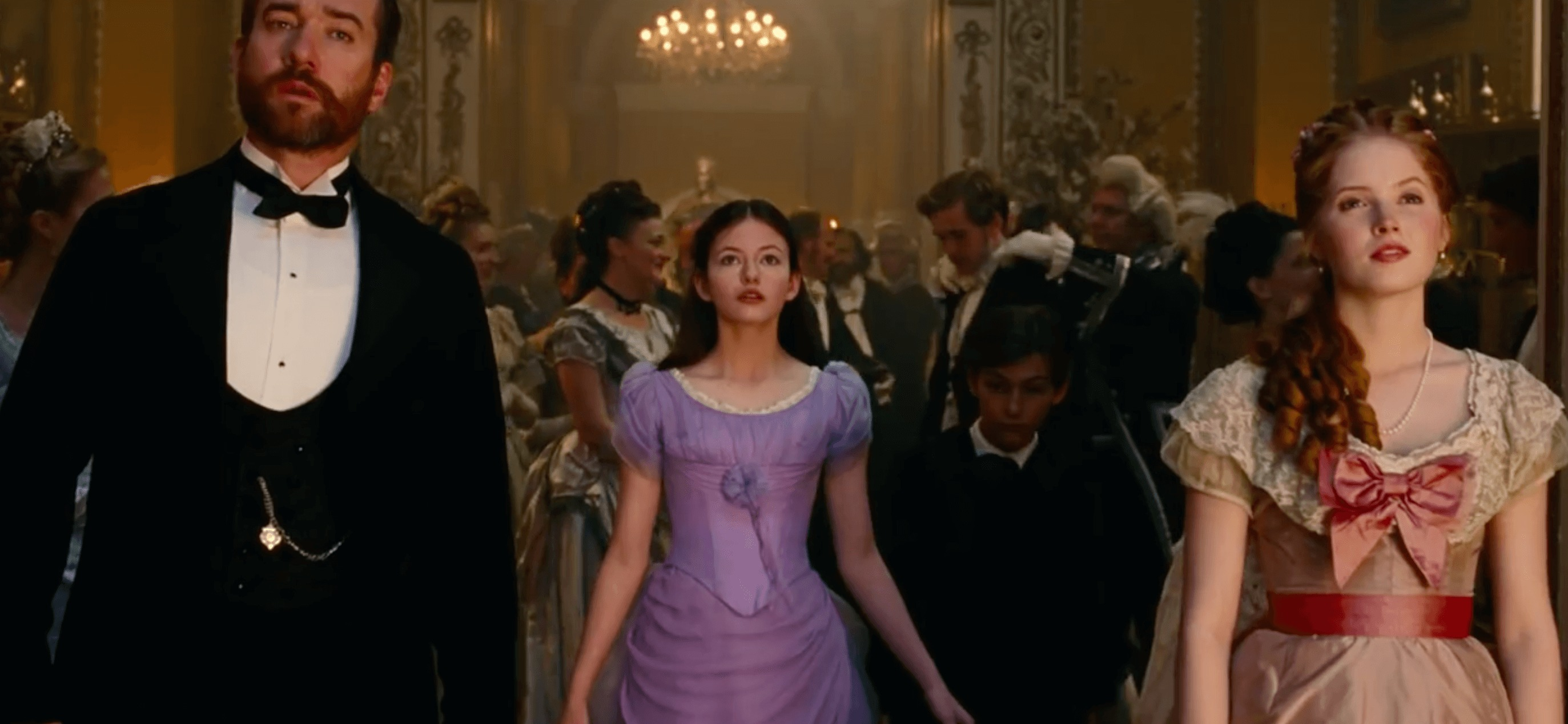 A young girl in a purple ballgown looks up in awe as she enters a Christmas party.