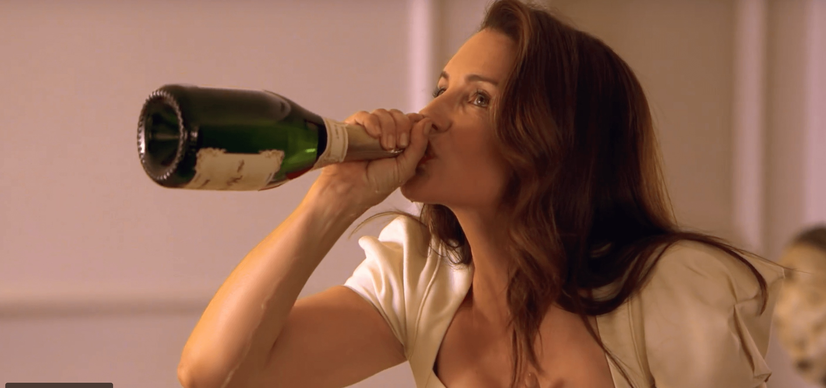 A brown-haired woman is chugging champagne from the bottle.