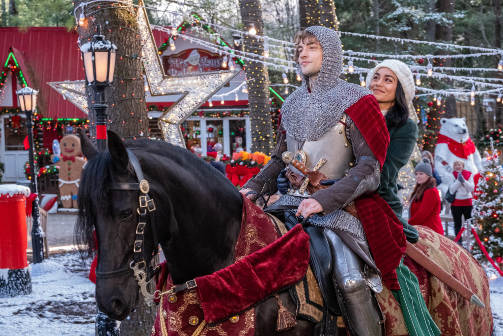 A man in chain armor and a woman in winter clothing smile as they ride a horse through town.