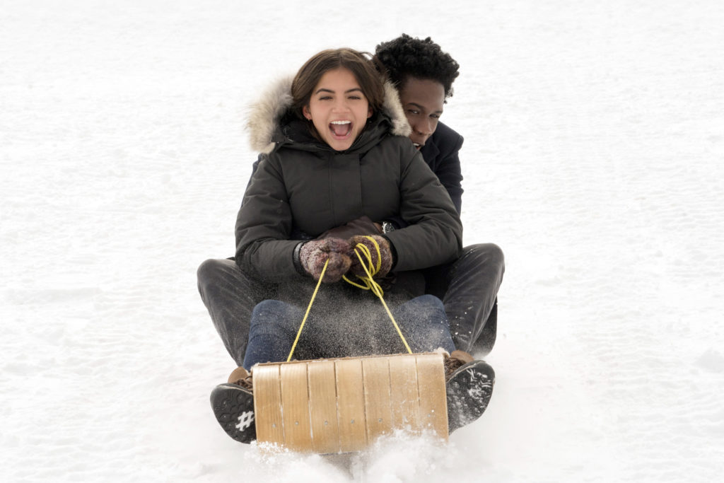 A young boy and girl laughing as they sled down a slope.