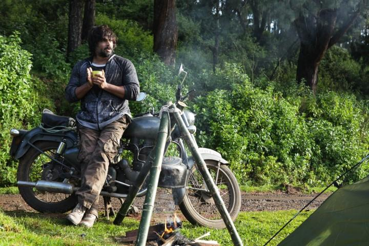 A ruggedly built Indian man is leaning against his motorbike out in the fields and gazing thoughtfully.