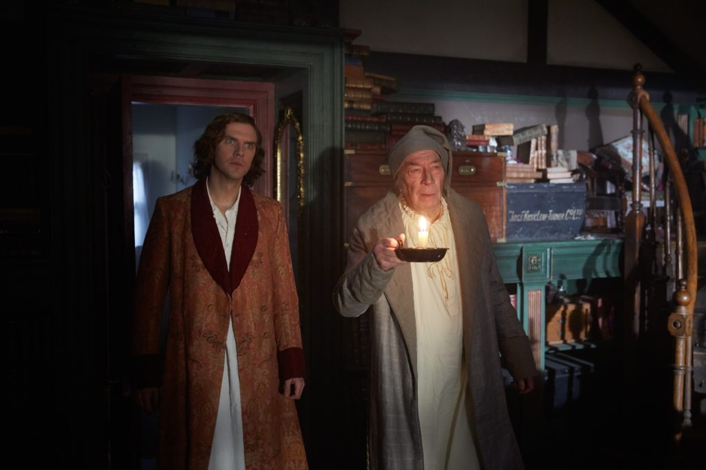 Two men - one old, one young - stare ahead in befuddlement. The older man is holding a candle in one hand.