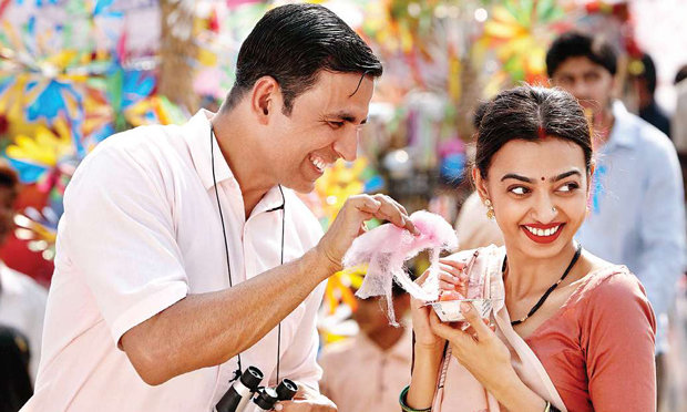 A still from Bollywood film Padman where the married couple are enjoying food and company.
