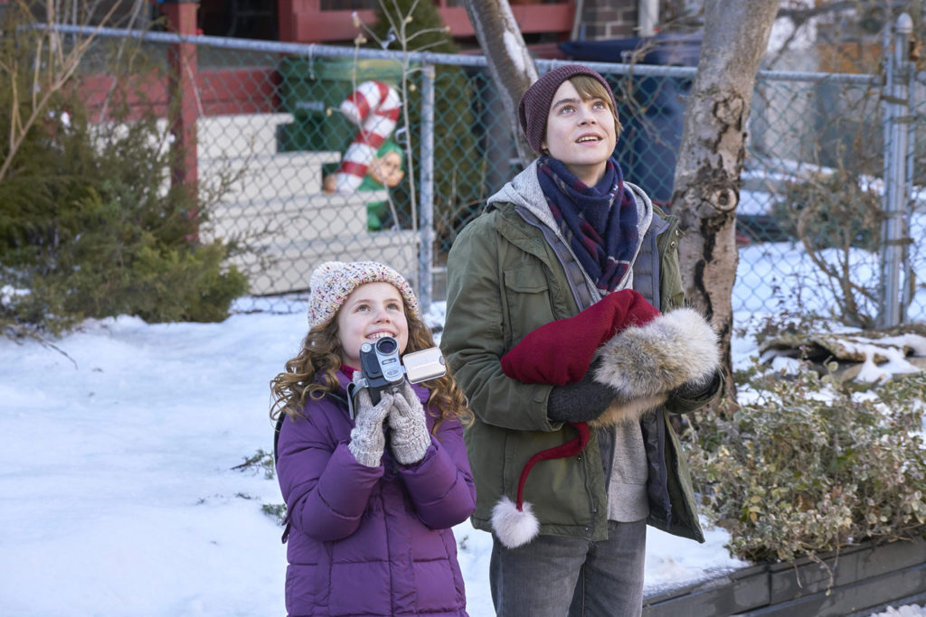 A young girl and teenage boy smile as they look up at the sky. The girl is holding a video camera.